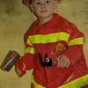 daddy bought halloween costomes early--and a certain little guy didn't want to go to school today so he could wear it.  (he did go to school but got to wear the costume after dinner.) i'm all for cute toys and such to go with the theme--but am puzzled as to why there was a big hatchet and a small fire extinguisher included in the set??   regardless--he made me smile so much tonight. what a character!